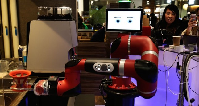 Robot barista named Sawyer makes a coffee at Henn-na Cafe, Japanese meaning Strange Cafein Tokyo, Friday, Feb. 2, 2018 (AP Photo)