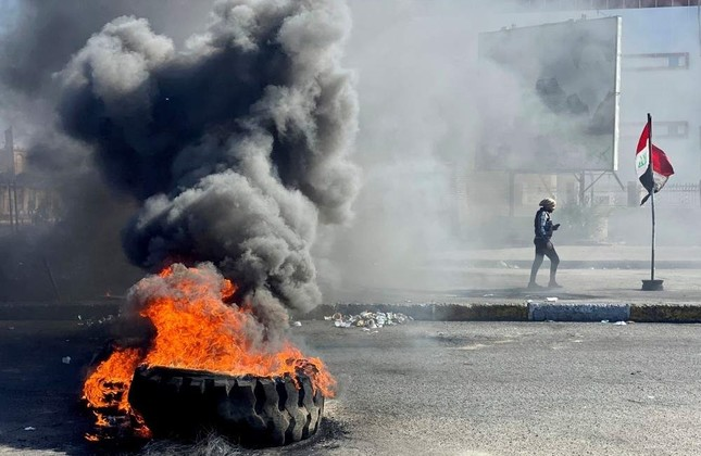 An Iraqi demonstrator walks past burning tires as they block a road during an anti-government protest, Nassiriya, Jan. 27. REUTERS Photo
