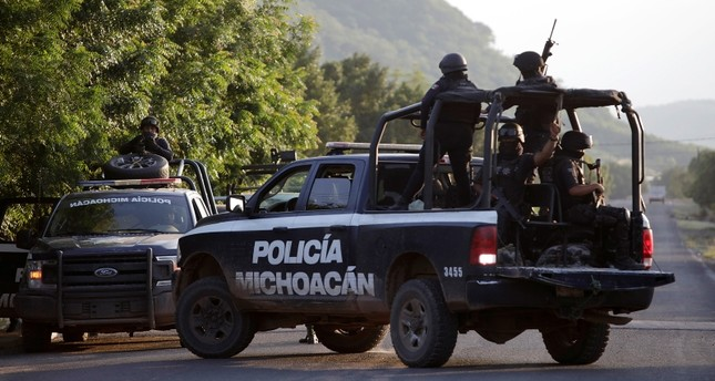 Security forces patrol along a road after police officers were killed during an ambush by suspected cartel hitmen in El Aguaje, in Michoacan state, Mexico October 14, 2019. (Reuters)