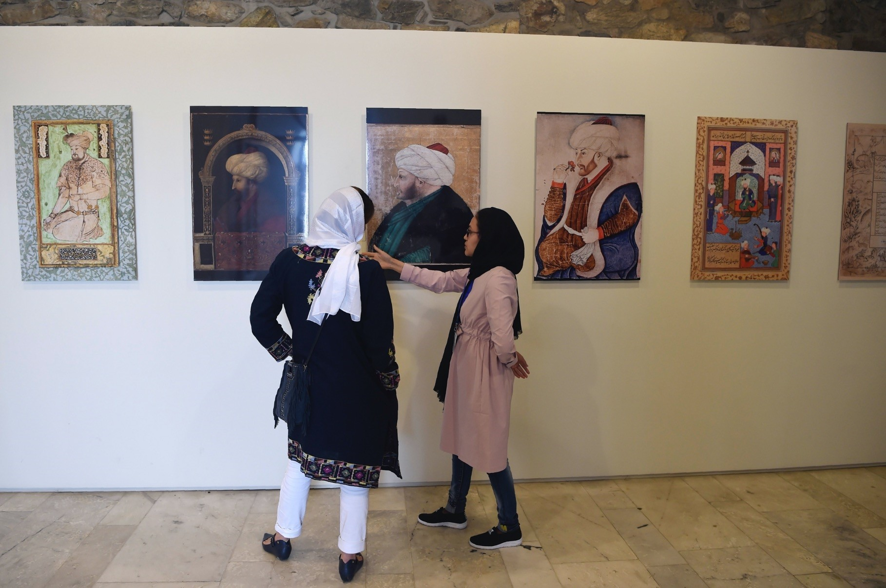 Afghan visitors walk past the display of Mughal paintings at the u201cKing Baburu2019s Kabul, Cradle of the Mughal Empireu201d exhibition in Kabul.