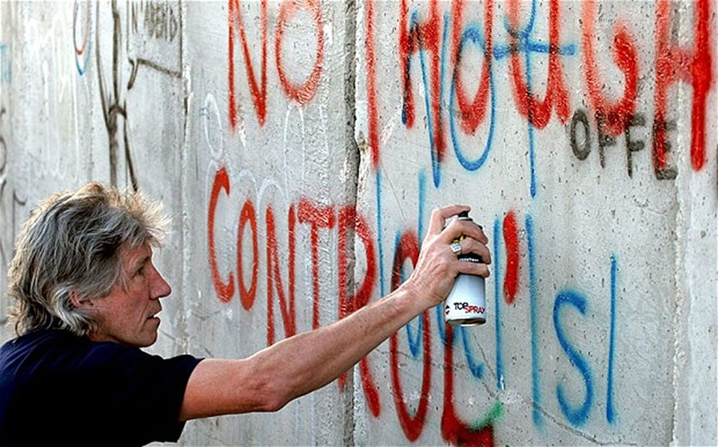 British rock musician and Pink Floyd co-founder Roger Waters spray-paints the words ,No Thought Control, on a section of what Palestinians call Israel's ,apartheid wall, in the West Bank town of Bethlehem, June 21, 2006. (AP Photo)