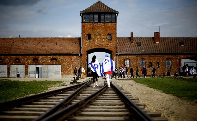 This June 25, 2015 file picture shows Brzezinka or Birkenau nazi death camp near Oswieciem, Poland, when young visitors with Israeli flags walk on railway tracks on the grounds of the former German Nazi death camp Auschwitz-Birkenau. (AP Photo)