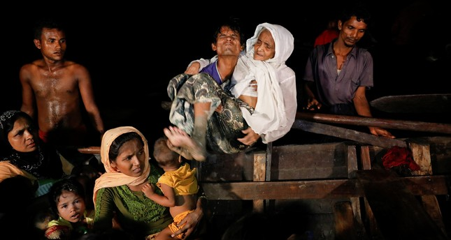 A man lifts an elderly woman from the boat as hundreds of Rohingya refugees arrive from Myanmar to the shore of Shah Porir Dwip, in Teknaf, near Cox's Bazar in Bangladesh, September 27, 2017. (AFP Photo)