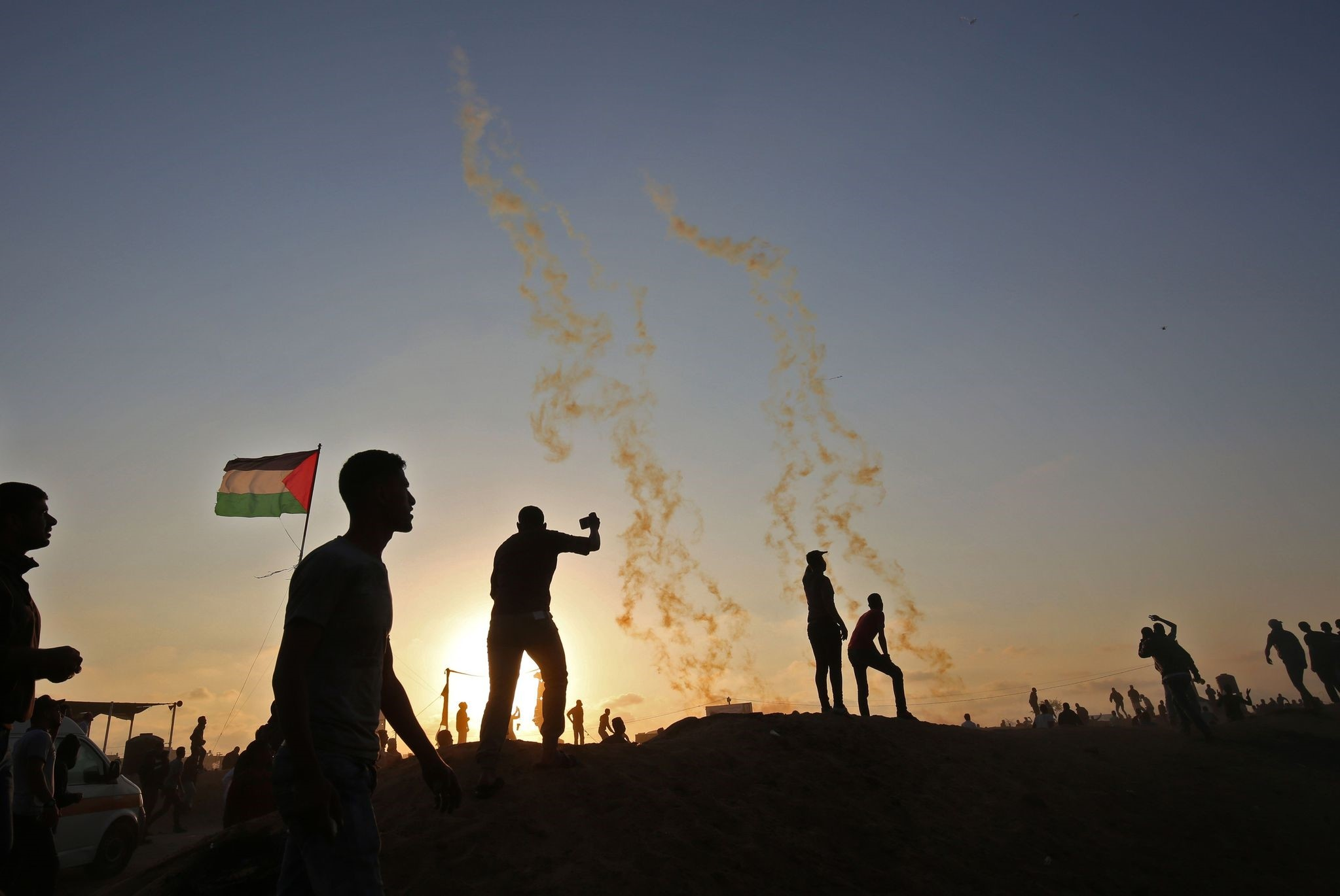 Palestinians protest as tear gas fumes erupt near the border with Israel in the southern Gaza Strip on May 15, marking 70th anniversary of Nakba.
