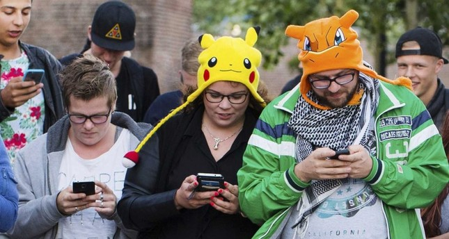 People play 'Pokemon Go' on their smartphones in Leerdam, the Netherlands. Pokemon Go, a Global Positioning System (GPS) based augmented reality mobile game, launched first on July in the U.S.