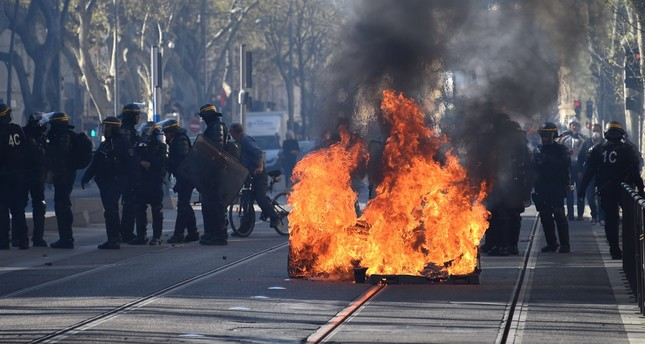 Riot police stand guard in front of a fire during clashes with 'yellow vest' protesters, Montpellier, March 23, 2019.