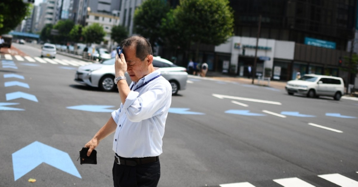 A man wipes his face as he crosses a street during a heatwave in Tokyo on August 1, 2019. (AFP Photo)