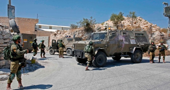 Israeli troops block a road during a house-to-house search operation in the West Bank village of Beit Fajjar near Bethlehem on Aug. 8, 2019 (AFP Photo)