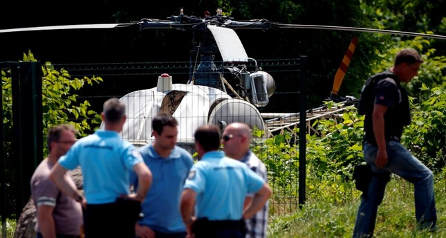 This picture taken in Gonesse, north of Paris shows police near a French helicopter Alouette II abandoned by French armed robber Redoine Faid after his escape from prison in Reau. (AFP Photo)
