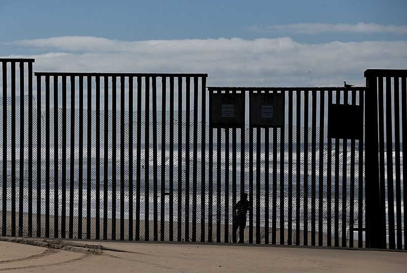 A man looks on from the Mexico side of the U.S. and Mexico border fence near Border Field State Park on February 4, 2017 in San Diego. (AFP Photo)