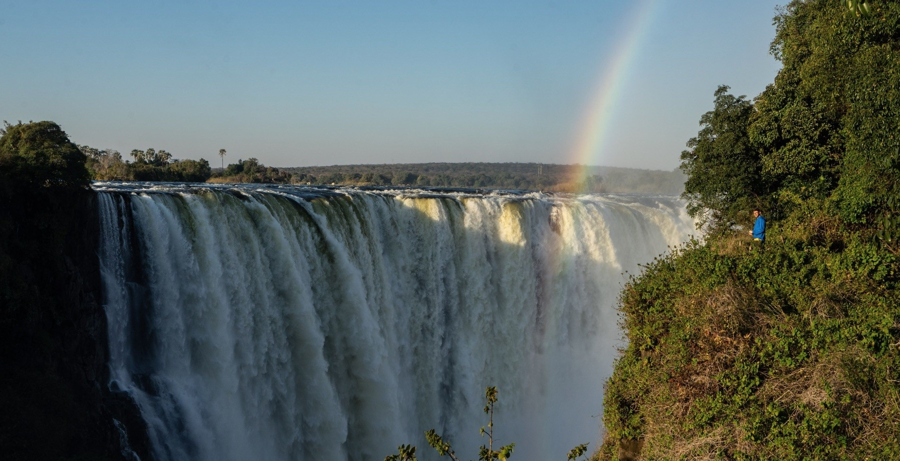 A tourist enjoys a view of the waterfalls from the u2018Devilu2019s Cataractu2019 where water rumbles down from a height of 73 meters at Victoria Falls.