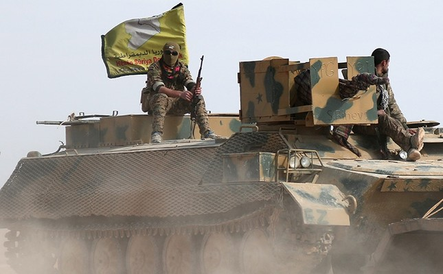 Syrian Democratic Forces (SDF) fighters sit on an armored vehicle in the north of Raqqa city, Syria, Feb. 05, 2017. The initials YPG are marked in on top of the shooting position in front of the vehicle. (Reuters Photo)