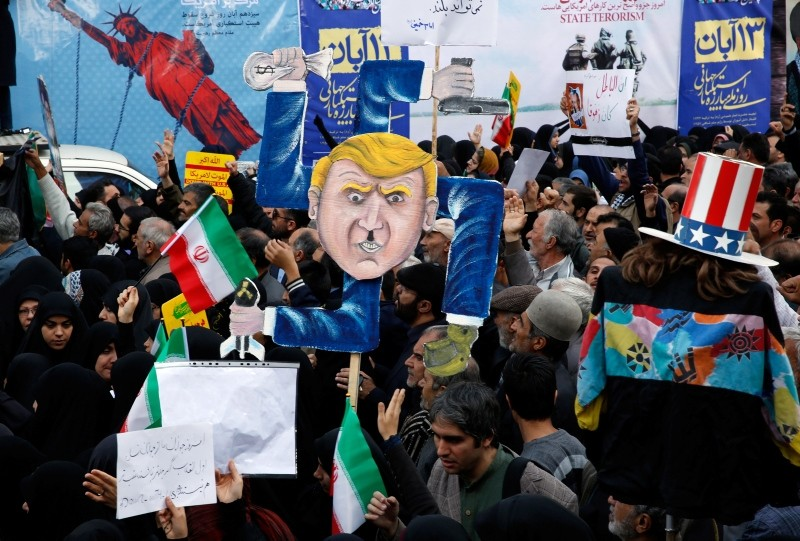Iranians hold a placard showing a caricature of U.S. President Donald J. Trump during an anti-U.S. demonstration marking the 39th anniversary of U.S. Embassy takeover, in front of the former U.S. embassy in Tehran, Iran, Nov. 04 2018. (EPA Photo)