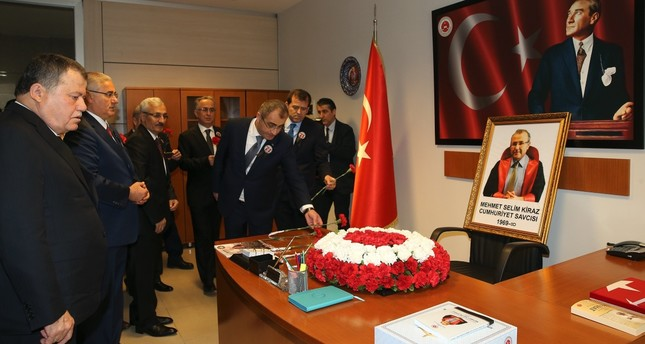 Colleagues place flowers on the desk of Mehmet Selim Kiraz on the anniversary of his death in 2017.