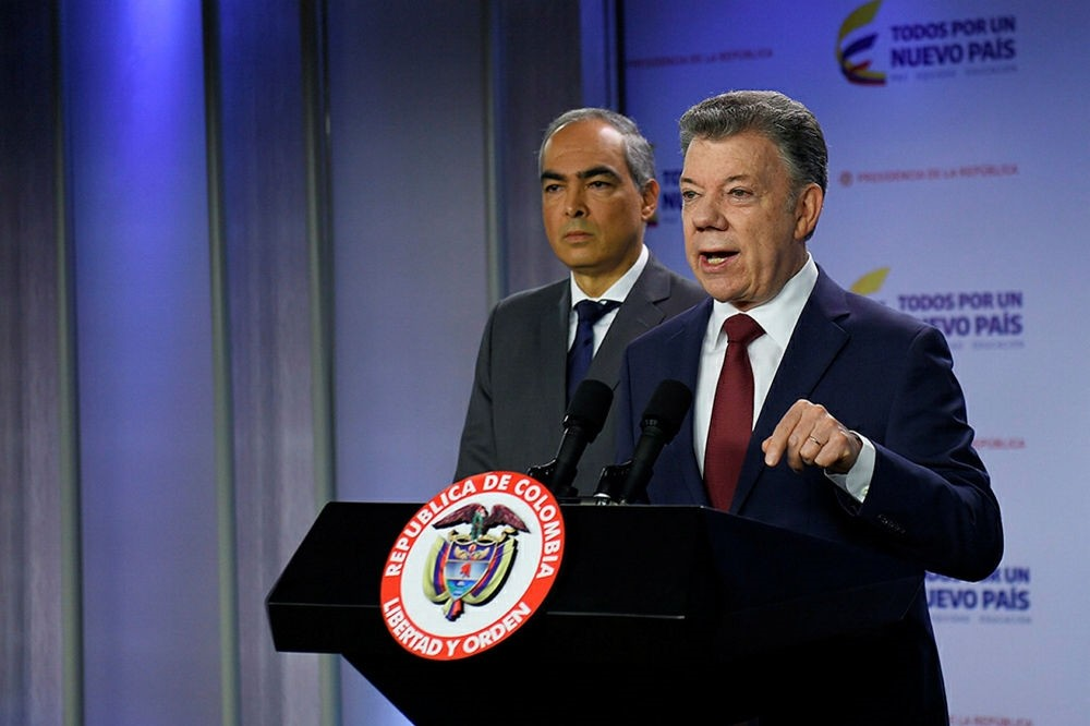 Colombian President Juan Manuel Santos (R) speaks next to Peace Commissioner Rodrigo Rivera at the Narino presidential palace, Bogota, Jan. 10.