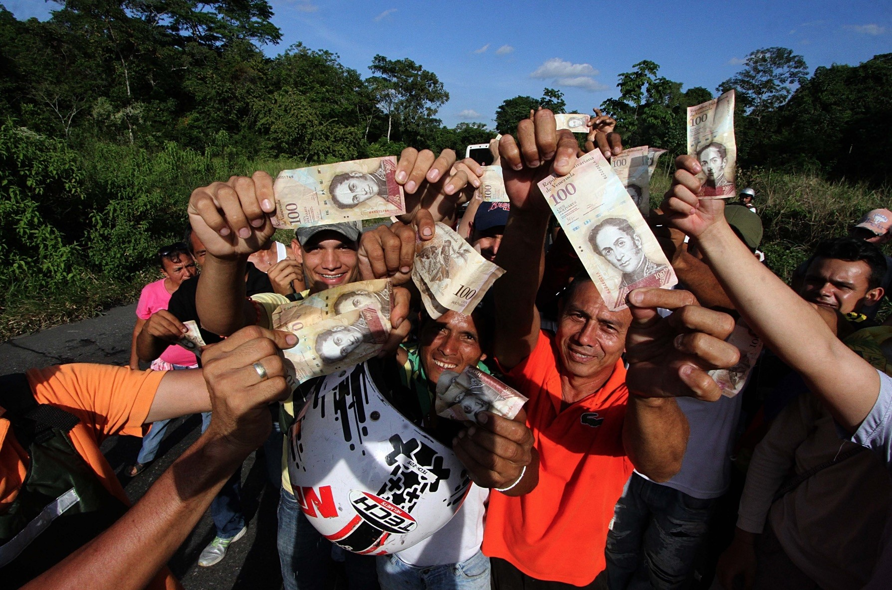 People hold up 100-Bolivar notes during a protest over the lack of cash as the new bank notes have not yet appeared, in San Cristobal in Venezuelau2019s Tachira state, last year.