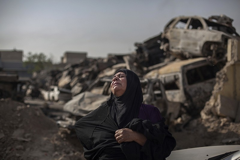 In this Oct. 9, 2017, photo, Fatima Ahmed Aswad cries as the body of her 15-year-old daughter Sana is exhumed in Mosul for forensic investigation in order to receive a death certificate. (AP Photo)
