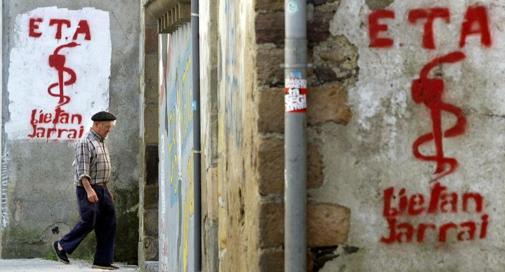 An old man walks past graffiti depicting the logo of Basque separatist group ETA in Goizueta, Spain. (Reuters Photo)