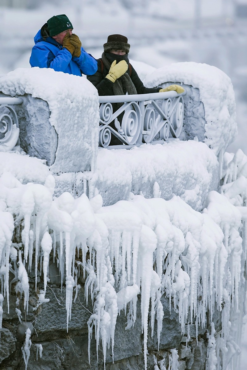 Visitors try to keep warm at the brink of the Horseshoe Falls in Niagara Falls, Ontario, as cold weather continues through much of the province on Friday, Dec. 29, 2017.