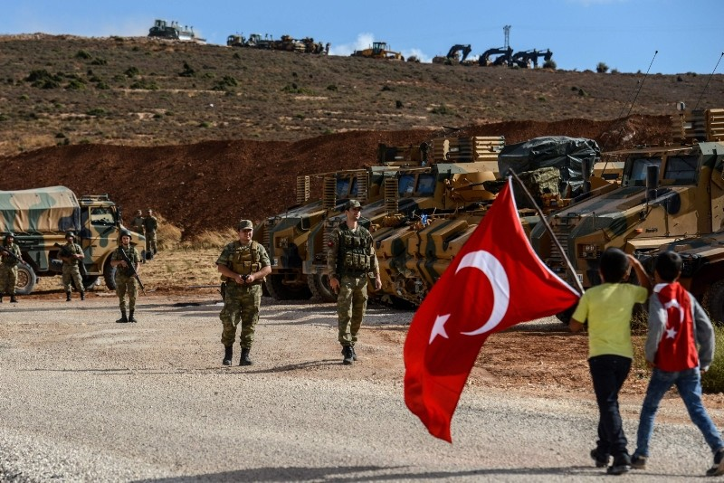 Turkish soldiers stand near armored vehicles as two young boys holding Turkish flags arrive during a demonstration in support of the Turkish Armyu2019s Idlib Operation. (AFP Photo)