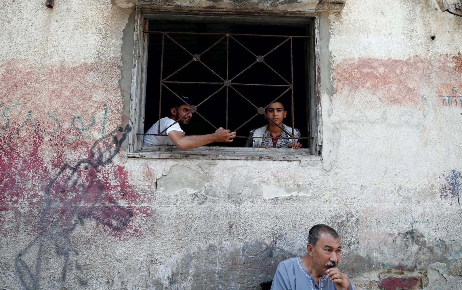 Palestinians look out of the window of their home at the Al-Shati refugee camp, Gaza City, Sept. 3.