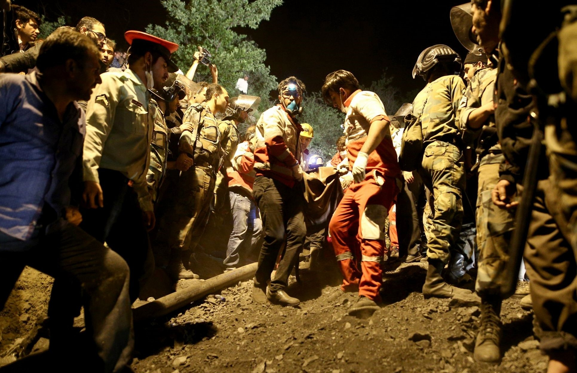 Rescue workers carry the body of a coal miner after he was pulled out from a mine in Azadshahr, in northern Iran. (AFP Photo)