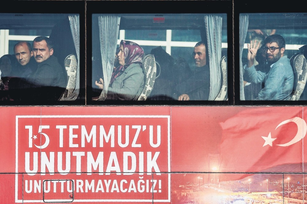Relatives of victims who were killed on the Bosporus Bridge gesture as they arrive by bus with a sign reading: u201cWe did not forget July 15, we will not let it be forgottenu201d