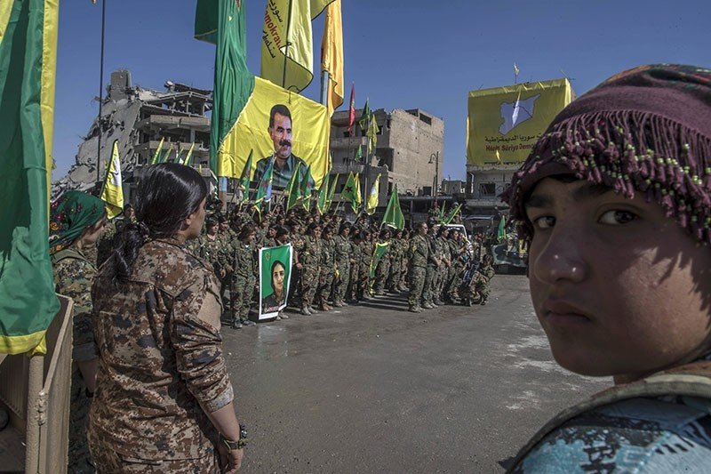 In this Thursday, Oct. 19, 2017 photo, militants from the PKK-affiliated Women's Protection Units (YPJ) hold a celebration in Paradise Square in Raqqa, Syria. The giant poster behined them features PKK's jailed leader Abdullah u00d6calan. (AP Photo)