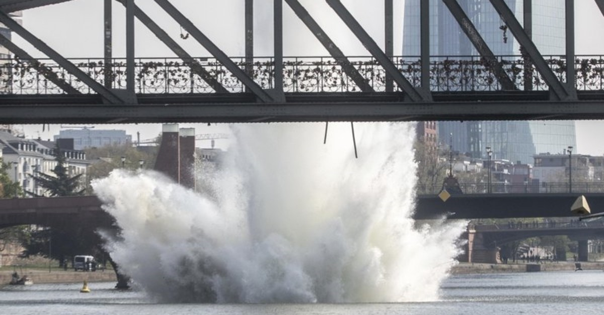 A large water fountain rises behind the Iron Bridge when a 250 kilogram US-American bomb from the Second World War in the Main River is detonated with a blast in Frankfurt, Germany, Sunday, April 14, 2019. (EPA via AP Photo)