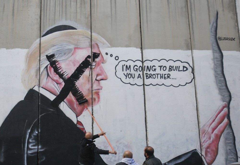 A Palestinian paints over a mural of President Trump during a protest in Bethlehem, West Bank, Dec. 7.