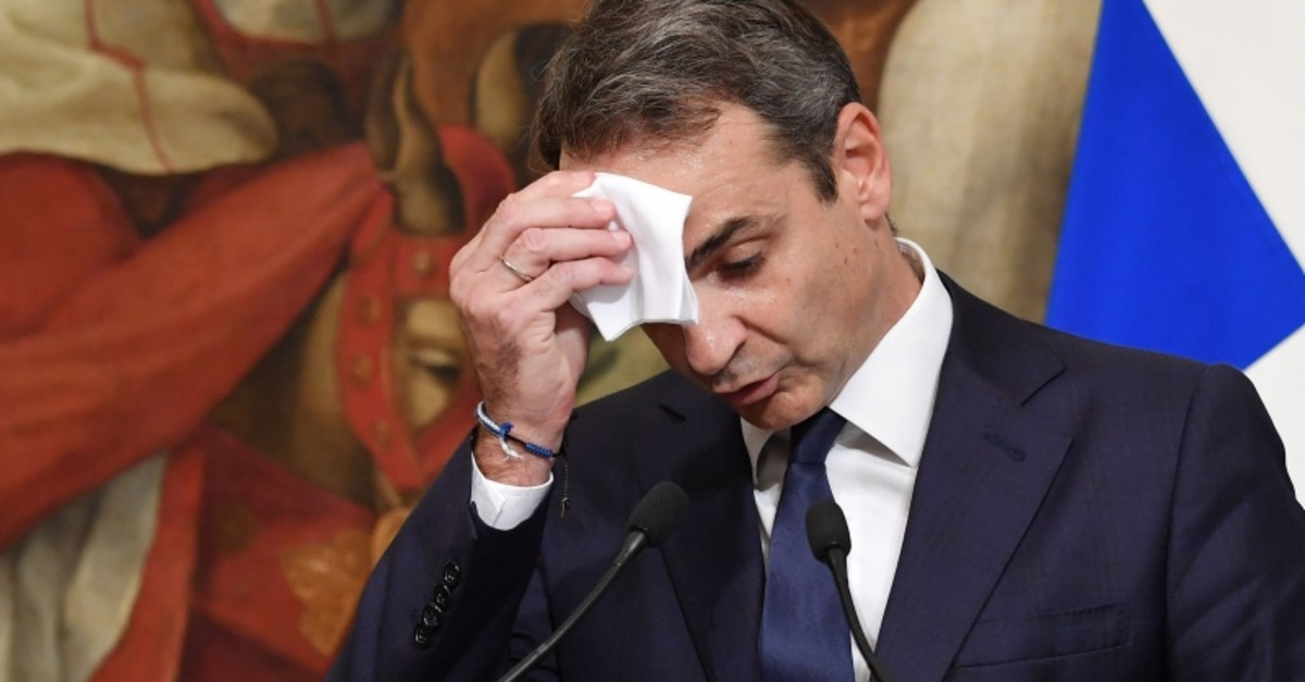 Greek Prime Minister Kyriakos Mitsotakis wipes his forehead during a joint press conference with his Italian counterpart following their meeting at Palazzo Chigi on November 26, 2019 in Rome. (AFP Photo)