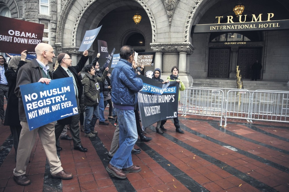 People protest the then U.S. presidential candidate Donald Trump's campaign pledge to register Muslims in the country, in front of his hotel in Washington D.C.