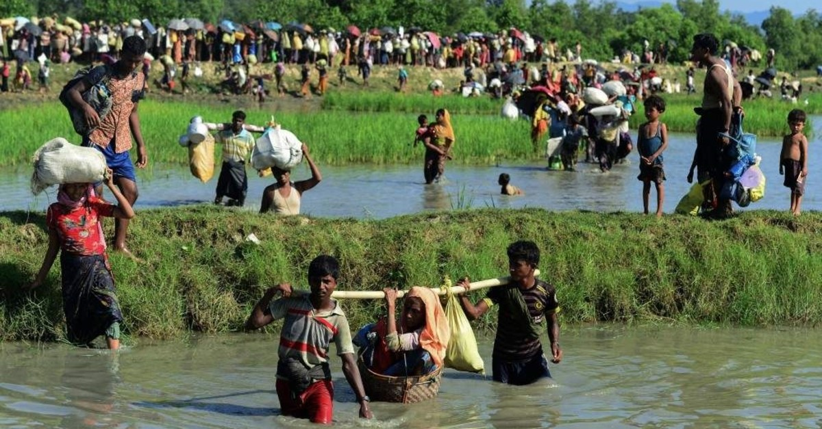 In this file photo taken on Oct. 16, 2017, Rohingya refugees carry a woman over a shallow canal after crossing the Naf River as they flee violence in Myanmar to reach Bangladesh. (AFP Photo)