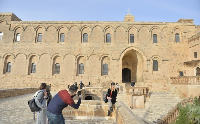 Tourists take photos in front of the Deyrulzafaran Monastery of Mardin. This Syriac Orthodox venue, known as saffron monastery for the color of its stone is among the city's top touristic attractions.