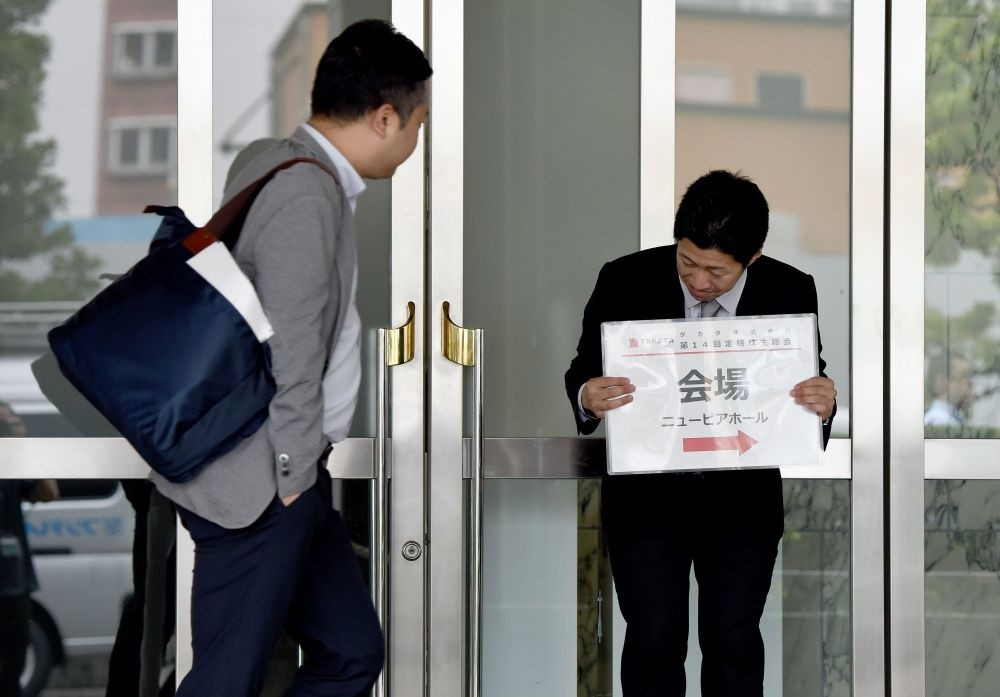 A staff member (R) holds a placard guiding shareholders to the venue of the annual shareholdersu2019 meeting of Japanu2019s crisis-hit car parts maker Takata in Tokyo.