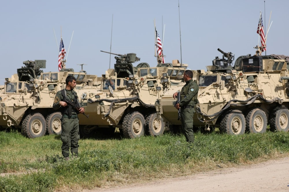 People's Protection Units (YPG) terrorists stand near U.S. military vehicles in the town of Darbasiya next to the Turkish border, April 29, 2017.