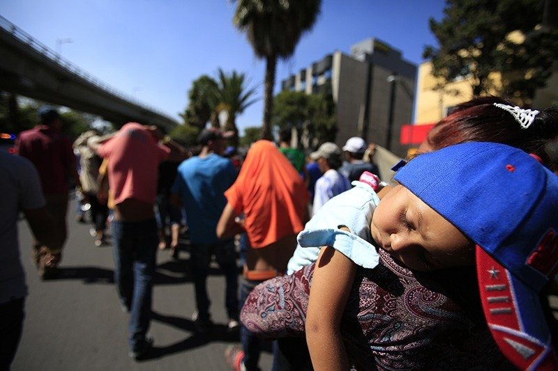 A sleeping Honduran girl is carried as a group of Central American migrants walk toward the U.S. border. (AP Photo)