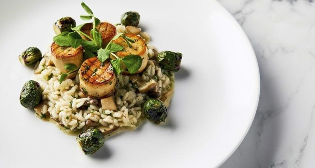 This image released by the Golden Globe Awards shows a dish of king oyster mushroom scallops on a bed of wild mushroom risotto with roasted Brussels sprouts, prepared by Beverly Hilton Executive Chef Matthew Morgan. Golden Globe Awards via AP
