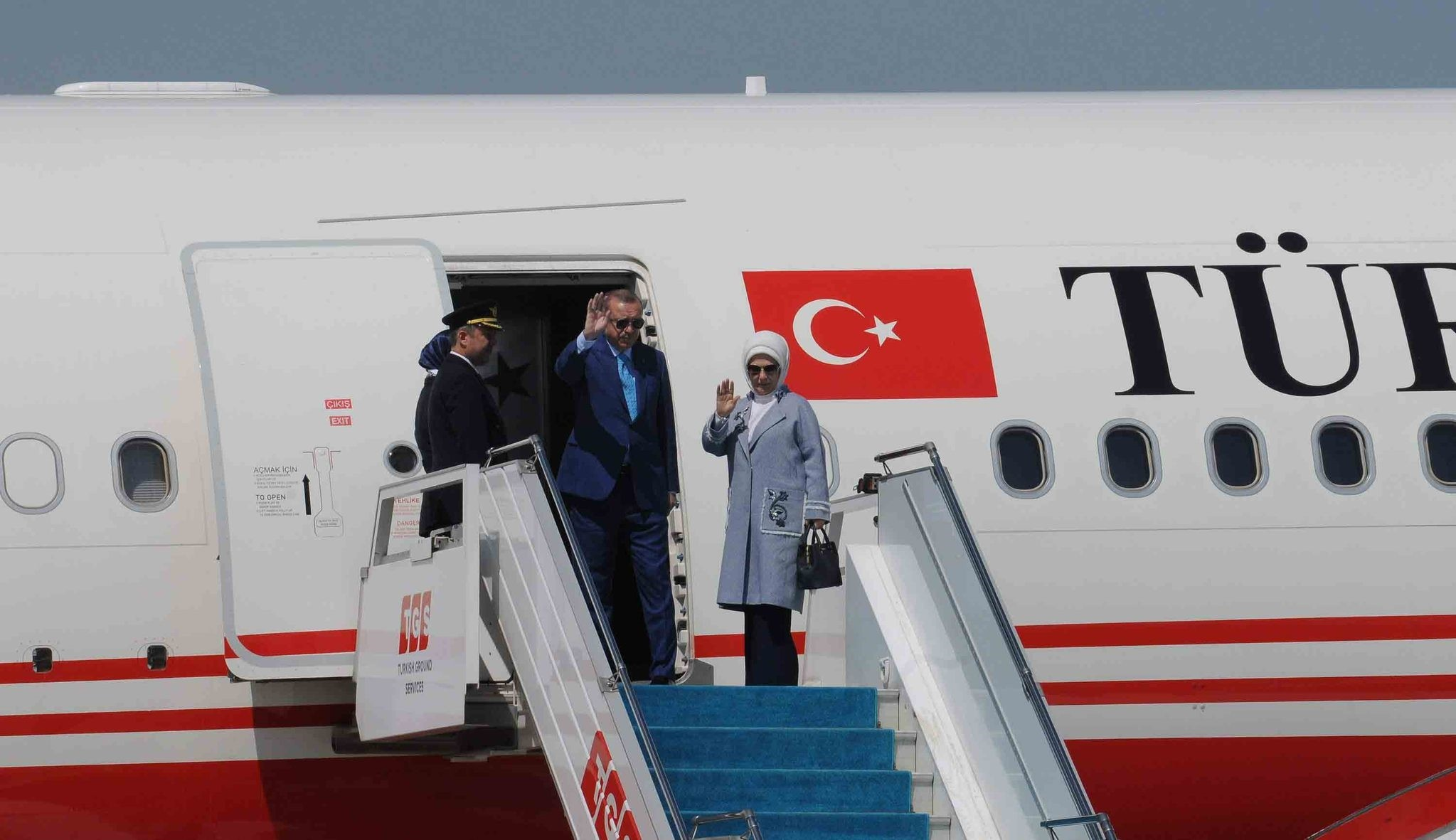 President Erdou011fan and First Lady Emine Erdou011fan wave before their departure for an official visit to India.