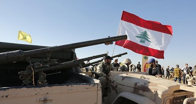 عناصر من حزب الله يرفعون العلم اللبناني إلى جانب علم الحزب (EPA)
