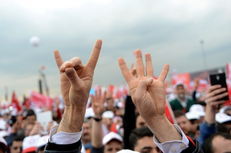 A man's hands seen making the ,grey wolf,, left, and rabia signs during a political rally in Istanbul.
