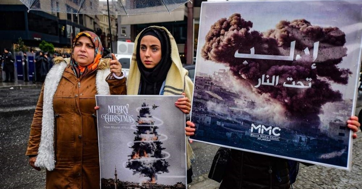 Protestors hold placards reading ,bomb Christmas tree, during a protest against the Syrian military operation in Idlib, northwestern Syria, taking place near the Russian Consulate, in Istanbul, on Dec. 28, 2019 (Photo by Yasin AKGUL / AFP)