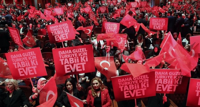 People hold banners and wave Turkish flags during a meeting with the Turkish President as part of the campaign for the constitutional referendum, Ankara, March 29, 2017.