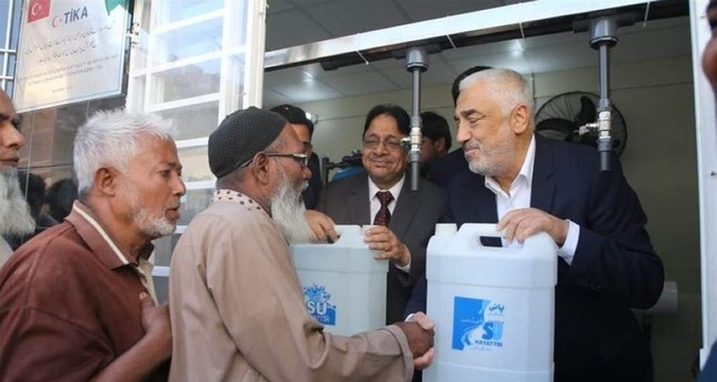 TIKA officials handing out bottles of filtered water to Pakistanis, Sindh, Pakistan. (AA Photo)