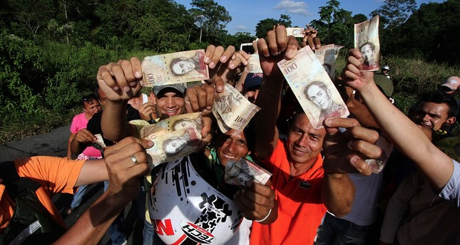 People hold up 100-Bolivar notes during a protest over the lack of cash as the new bank notes have not yet appeared, in San Cristobal in Venezuela's Tachira state, last year.