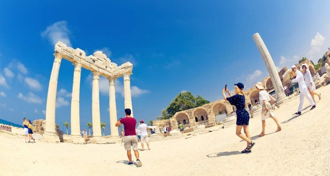 Tourists take pictures of the ancient monumental stone arch of Temple of Apollo in Turkey's southwestern Ayd?n province, July 26, 2019. iStock Photo