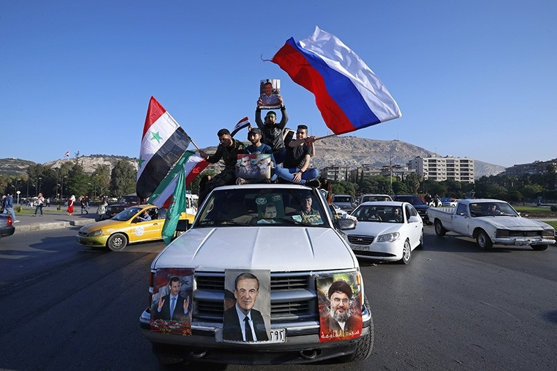 Regime supporters wave Syrian, Iranian and Russian flags as they chant slogans against U.S. President Trump during protests agains U.S.-led strikes in Damascus, Syria, Saturday, April 14, 2018. (AP Photo)