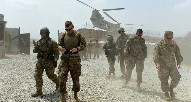U.S. army soldiers walk as a NATO helicopter flies overhead in the Khogyani district in the eastern province of Nangarhar, Afghanistan.