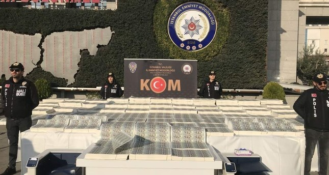 Police officers stand next to seized counterfeit U.S. dollar bills displayed in the courtyard of Istanbul Security Directorate, Jan. 15, 2019. AA Photo