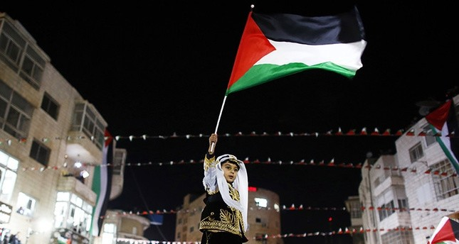 A Palestinian boy in traditional clothes waves a Palestinian flag during a rally in the West Bank city of Ramallah November 29, 2012 (Reuters Photo)